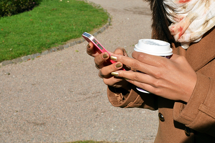 Hands holding a mobile phone and coffe cup.